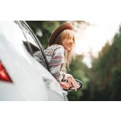 Happy hipster girl traveling adventure vacations. Boho woman sitting in car looking from window on beautiful view in country road